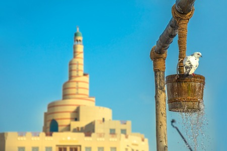 Pigeon drinks water at old well fountain, iconic landmark in the middle of Souq Waqif in Doha city center, Qatar. Middle East, Arabian Peninsula. Sunny blue sky. Doha Mosque on blurred background.