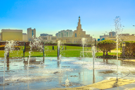 Water fountain at Souq Waqif Park in Doha Corniche with Doha spiral Mosque and Minaret on background. Doha center in Qatar, Middle East, Arabian Peninsula in Persian Gulf. Sunny day with blue sky.