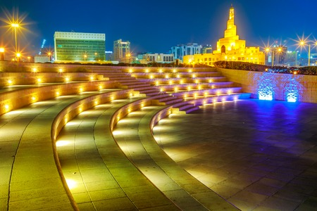 Stairs of amphitheater at Souq Waqif Garden near Doha Corniche with Doha mosque illuminated at night. Doha city center in Qatar, Middle East, Arabian Peninsula in Persian Gulf.