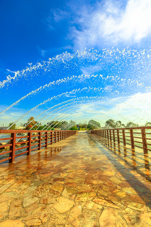 Bridge with fountain in Aspire park, Dohas biggest park, located in Aspire Zone, Doha Sports City, Qatar, Middle East. Popular place for Qatari families. Vertical shot.