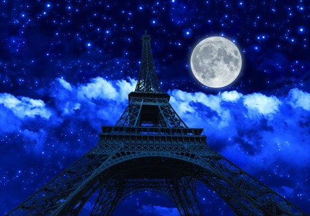 night sky with clouds and big full moon at night with backlit Eiffel Tower. Paris in France. Stock Photo