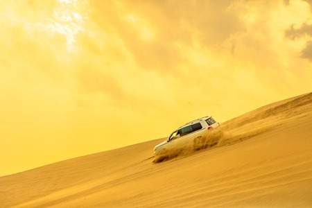 Dune Bashing at sunset sky near Qatar and Saudi Arabia. Khor Al Udeid, Persian Gulf, Middle East. Inland sea is a major tourist destination for Qatar. Discovery and adventure travel concept.