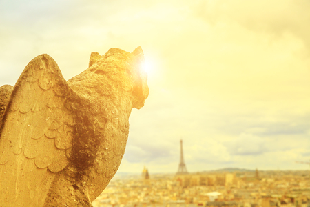 close up of a mythological gargoyle statue of Notre Dame cathedral on Paris skyline at sunset. Paris city of France. Aerial view of the gothic church Our Lady of Paris with Eiffel Tower on the horizon