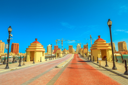 Walkway towards the construction of the new luxury hotel on a central islet at Porto Arabia, the Pearl-Qatar, Doha, Persian Gulf in the Middle East. Sunny blue sky. Copy space.