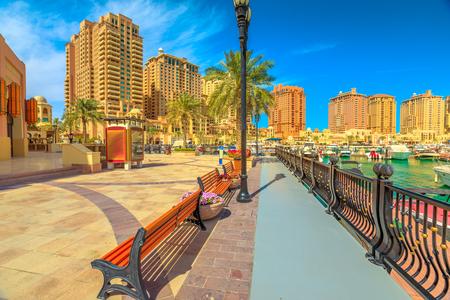 Bänke und Palmen entlang der Promenade des Yachthafens in Porto Arabia am Pearl-Qatar, Doha, mit Wohntürmen und Luxusbooten im Hintergrund. Persischer Golf im Nahen Osten. Sonniger Tag. Standard-Bild