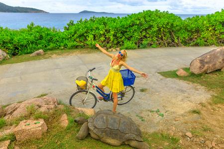 Glückliche kaukasische Lifestyle-Touristenfrau auf dem Fahrrad in der Nähe von Anse Banane in La Digue, Seychellen, mit Aldabra-Riesenschildkröte, Aldabrachelys gigantea. Beliebte Touristenattraktion. Natürlicher Meereshintergrund. Standard-Bild