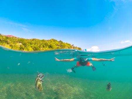 Vue fractionnée de l'apnée féminine sous et au-dessus de la mer. Robe de plongée en apnée femme à Felicite, île satellite de La Digue, Seychelles. Activité de sports nautiques de style de vie de voyage. Poissons et vie marine au premier plan.