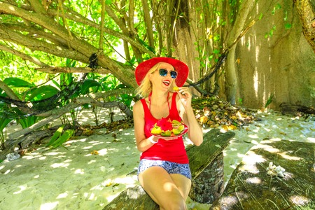 Tourist woman in red sunhat eats fresh local fruit plate at Anse Source dArgent, La Digue under palm trees. Lifestyle female enjoy on tropical beach at Seychelles. Healthy exotic summer diet.