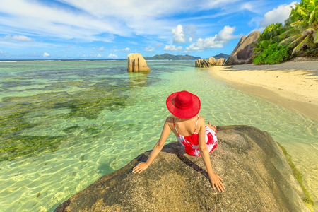 Tourist woman in red hat on a granite boulder at Anse Source dArgent. Elegant female looks turquoise sea of Indian ocean on La Digue Island, Seychelles.Aerial view of tropical beach, scenic landscape