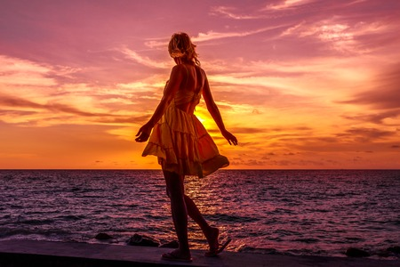 Elegant lifestyle woman in yellow dress at Anse Kerlan, Seychelles looking scenic colorful sky. Kerlan Beach in Praslin is famous for spectacular sunsets on Cousine and Cousin islands. Luxury holidays