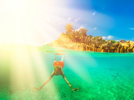 Scenic sunbeams of coral reef landscape in Seychelles. Female apnea underwater at St. Pierre Island. Snorkeling woman exploring sea life of Indian Ocean, under and above water photography.