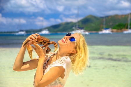 Tourism in Seychelles, Africa, Indian Ocean. Happy tourist woman holding an Ocypode Ceratophthalmus also called Ghost Crab with one claw being larger than the other. Curieuse Island Nature Reserve.