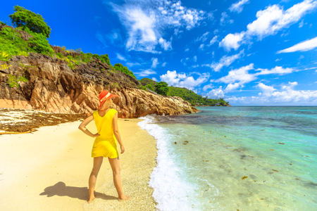 Lifestyle female in yellow looking turquoise sea and pristine white beach of remote Anse La Blague, southeast of Praslin Island, Seychelles. Tourist woman on the shore in tropical holiday destinations