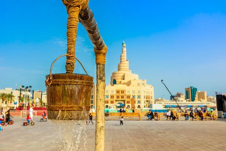 Closeup of flowing water at old well fountain, famous place in the middle of Souq Waqif, Doha center, Qatar. Middle East, Arabian Peninsula. Doha Mosque with minaret on blurred background. Blue sky.