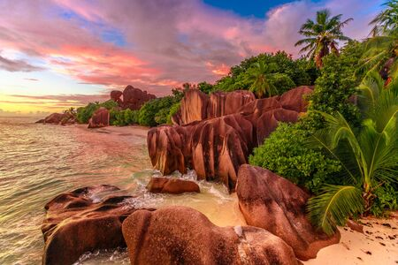 Dramatic colorful sky at twilight at scenic Anse Source dArgent Beach in Seychelles, La Digue. Aerial view of amazing landscape with huge shaped rock stone of granite and palm trees. Stock Photo