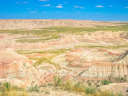 Surreal rock formations and pinnacles created be erosion over millions of years at Badlands National Park, South Dakota, United States. American travel destination. Blue sky in a sunny day.