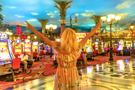 Happy winning caucasian woman at the casino of Las Vegas, Nevada, USA. Blonde lady enjoying spending money and being lucky enough to win. Architecture blur background. Gambling addict concept.