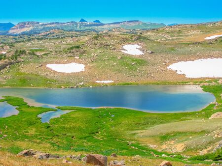 Alpine lake at Beartooth Pass on Beartooth Highway. Beartooth Mountains, Wyoming, United States. Scenic aerial landscape in summer season. Blue sky with copy space.