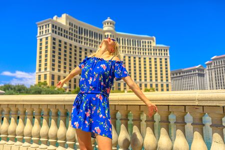 Blonde lady tourist travel vacation at Las Vegas city, Nevada, USA. Caucasian lifestyle woman with sunglasses enjoying on the balcony in Las Vegas strip. American travel summer holidays. Sunny daytime 写真素材