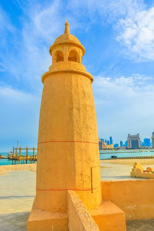Katara Beach lighthouse with wooden boats and West Bay skyline on background in Doha Bay area near Katara cultural village. Qatar, Middle East, Arabian Peninsula. Vertical shot. 写真素材