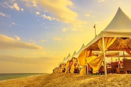Luxuriöse Zelte im Desert Beach Camp, Inland Sea, Khor al Udaid im Persischen Golf, Südkatar. Malerischer Sonnenunterganghimmel im Nahen Osten, Arabische Halbinsel. Das Binnenmeer ist ein wichtiges Touristenziel für Katar
