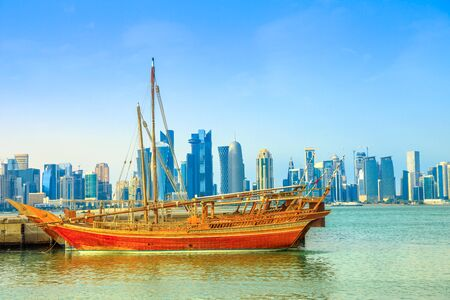 Traditional wooden dhow in foreground with seafront of Doha Bay and skyscrapers of West Bay skyline on background. Capital of Qatar, Middle East, Persian Gulf. Waterfront urban city.