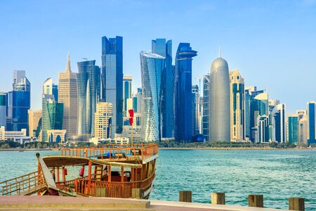 Traditional wooden dhow on foreground at Doha Bay and skyscrapers towers of West Bay skyline on background. Capital of Qatar, Middle East, Persian Gulf. Sunny blue sky. Urban modern cityscape. 写真素材 - 128238814