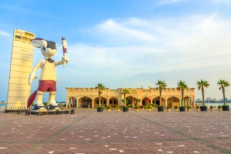 Doha, Qatar - February 23, 2019: Giant statue of Orry The Oryx, mascot of the Asian Games 2006 along the Corniche close to Al Mourjan luxury restaurant in Doha West Bay, Middle East. Sunset light shot