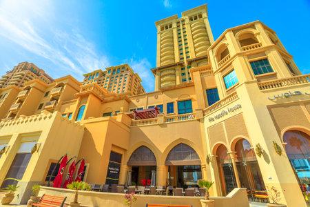 Doha, Qatar - February 18, 2019: Neighbors Coffee along marina walkway promenade in Porto Arabia at the Pearl-Qatar, Doha. Persian Gulf in Middle East. Sunny day with blue sky.