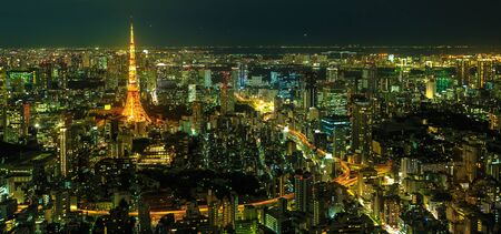 Panorama of Tokyo Skyline at night with illuminated iconic Tokyo Tower from Mori Tower, the modern skyscraper and tallest building of Roppongi Hills complex, Minato District, Tokyo, Japan. Aerial view 写真素材