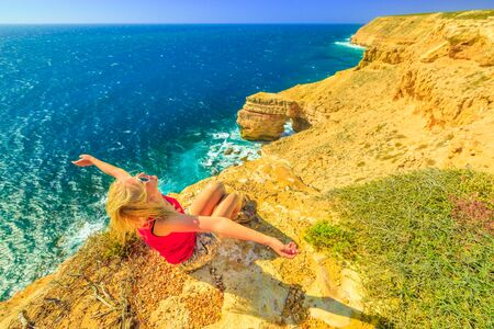 Backpacker girl with open arms at Natural Bridge in Kalbarri National Park, Western Australia. Happy woman on cliffs of Indian Ocean coastline in Australian Outback. Blue sky in summer. Copy space. 写真素材 - 128239160