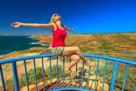 Coral coast, Indian Ocean, Australia. Carefree woman at Eagle Gorge Lookout platform in Kalbarri National Park, Western Australia. Caucasian girl enjoys in popular travel destination. Blue sky. 写真素材 - 128239174