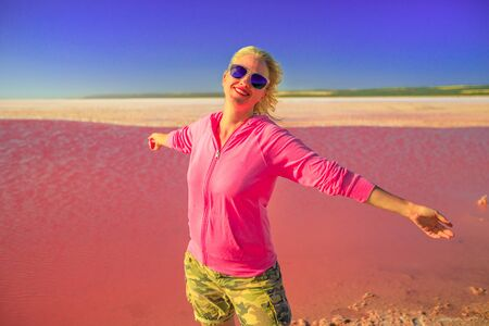 Freedom caucasian woman with open arms at Pink Lake in Port Gregory, Western Australia. Blonde tourist in Hutt Lagoon, Australia. Blue sky in summer holiday. Copy space. Pink color landscape. 写真素材 - 128239185