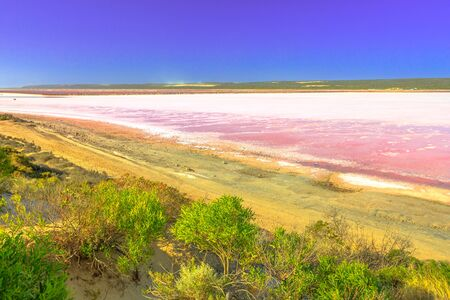 Pink Lake lookout over Salt Lake in Gregory, Western Australia. Aerial view of Hutt Lagoon in pink color for the presence of algae. Popular destination in Australia. Copy space. Blue sky.