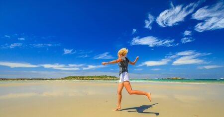 Active woman running on seashore of Madfish Bay in William Bay National Park, Denmark region, Western Australia. Carefree girl run in beach summer day in Australia. Copy space, blue sky. 写真素材 - 128239193
