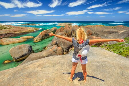 Happy woman on the cliffs above elephant-shaped rocks of Elephant Rocks in Western Australia. Young girl looking Great Southern Ocean in William Bay NP. Summer destination in Australia, Albany Region. 写真素材 - 128239204