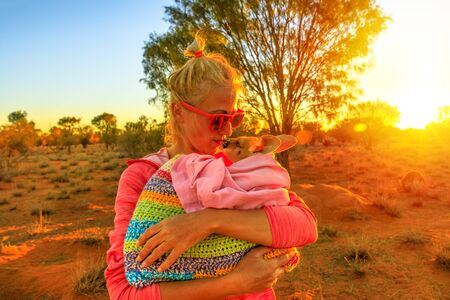 Tourist woman holding ed kissing kangaroo joey at sunset light in Australian outback. Interacting with cute kangaroo orphan. Australian Marsupial in Northern Territory, Central Australia or Red Center 写真素材