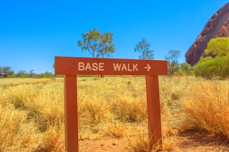 Uluru Base Walk sign in sand path of Uluru-Kata Tjuta National Park, Northern Territory, Central Australia, outback landscape. The popular base walk is 10 km around the circumference of the rock track 写真素材 - 130390761