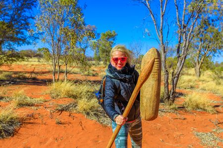 Happy tourist woman holding an aboriginal weapon of spear and a wooden shield used by Luritja and Pertame people, Central Australia, Northern Territory. Red sand and bush wilderness in desert outback. 写真素材 - 130390766