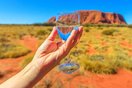 Womans hand holding a glass goblet that reflecting Ayers Rock in Uluru-Kata Tjuta National Park, Central Australia, Northern Territory. Toast in Australian outback, Red Center.