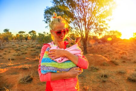 Tourist woman holding orphaned baby kangaroo at sunset sunlight in Australian outback. Interacting with cute kangaroo orphan. Australian Marsupial in Northern Territory, Central Australia, Red Centre.