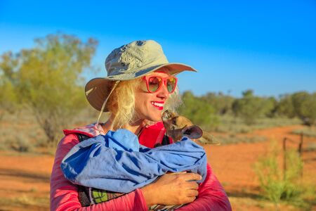 Tourist woman holding orphaned baby kangaroo in Australian outback, bush landscape. Interacting with cute kangaroo orphan. Australian Marsupial in Northern Territory, Central Australia, Red Centre.
