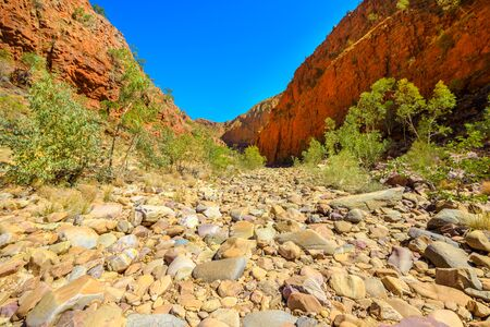 Dry Ormiston Gorge with red cliffs in West MacDonnell Ranges in Northern Territory, Central Australia Outback. Ormiston Pound walk is a popular circular walk trekking.