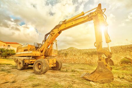 Side view of yellow excavator for building work along road in a suggestive construction site at sunset. Work in progress, industrial machine. Stock Photo