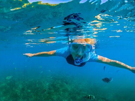 Porträt des Weibchens in Neoprenanzug-Apnoe auf den Seychellen, Indischer Ozean. Reise-Lifestyle-Wassersport-Aktivität. Junge kaukasische Frau, die im tropischen türkisfarbenen Meer schnorchelt. Frauenfreies Tauchen schwimmt im Korallenriff Standard-Bild