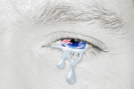 Crying eye with Australian Flag iris on black and white face. Concept of sadness and empathy for bushfire and natural disasters in Australia. Patriotic metaphor. Stock Photo