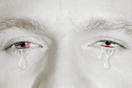Crying eyes with the American flag and Iranian flag in irises on black and white face. Concept of sorrow for world conflict and war, patriotic metaphor.