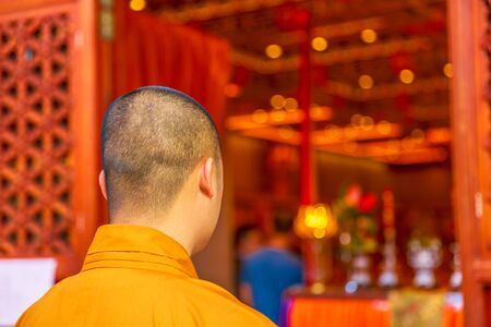 Hong Kong, China - December 11, 2016: monk in orange from behind inside the Po Lin Monastery of the Big Buddha, symbol of Lantau Island, Chinese destination. Editoriali