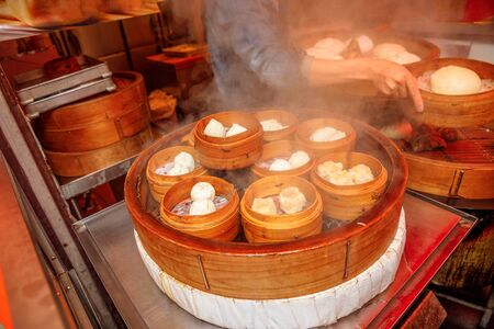 Closeup of asian steaming dumplings or dim sum, cooking in a wooden steamer in Yokohama Chinatown, the Japans largest Chinatown, central Yokohama. 스톡 콘텐츠