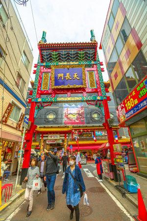 Yokohama, Japan - April 21, 2017: asian people wearing a mask walking in narrow street. Gate in Yokohama Chinatown, the Japans largest Chinatown on background. Pedestrian area. Vertical shot.